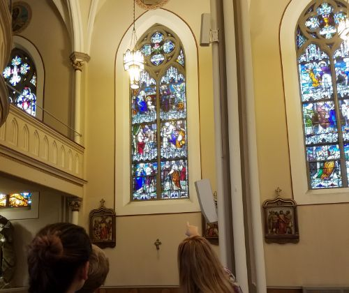 People point to a stained glass window