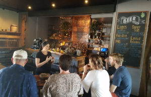 A woman talks to guests in the brewery bar.