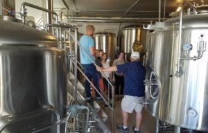 People stand between beer tanks.