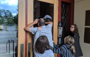 Guests peer into a glass door.