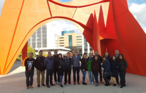 Group smile in front of Calder's red sculpture.