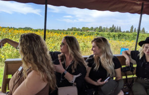 Women in vehicle look out over vineyards.