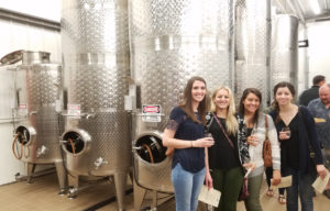 Three women stand in front of wine tanks.