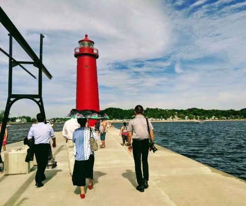 People on a stone jetty and a red lighthouse.